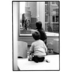 Kinderen kijkend door raam / analoge dokaprint (site = scan dokaprint)